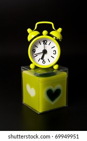 Lovely green clock on green candle isolated on black background