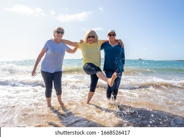 Lovely group of senior girl friends on their 60s walking and having fun splashing water on sea. Three mature healthy retired females Laughing and enjoying retirement and outdoors active lifestyle.