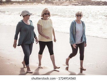 Lovely group of three active senior woman on their 60s walking, exercising and having fun on the beach. Mature females Laughing enjoying walk on vacation. Retirement and health lifestyle.