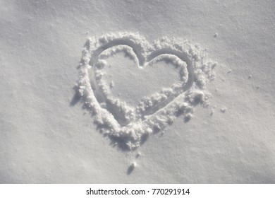 Lovely hand drawn sunny heart symbol in the fresh snow.
