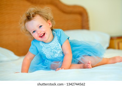 Lovely happy blonde toddler girl sitting on a bed in bedroom