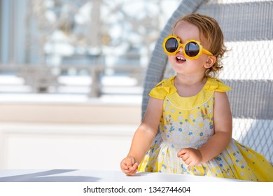 Lovely happy blonde toddler girl in sunglasses sitting in outdoor cafe