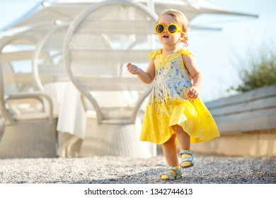 Lovely happy blonde toddler girl wearing yellow dress and sunglasses playing outdoors