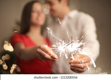 Lovely happy couple celebrating New Year's Eve at home with fireworks