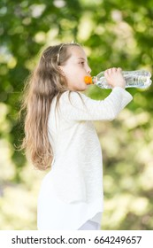 Lovely happy little girl drinking water at summer day