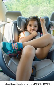 Lovely happy little girl sitting in a car seat with green trees background