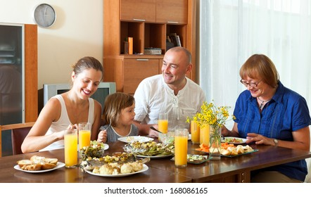 Lovely happy multigeneration family having healthy dinner at home together