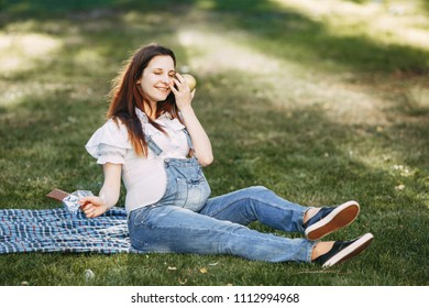 Lovely happy pregnant woman eating apple instead of chocolate. Healthy lifestyle, pregnancy diet, nutrition, good mood, intrauterine growth concept