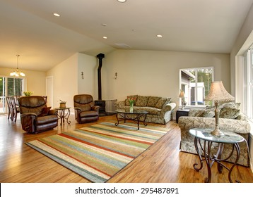 Lovely hardwood floor family room with recliners, sofas, and a striped rug.