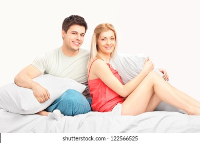 Lovely heterosexual couple in pajamas sitting on a bed