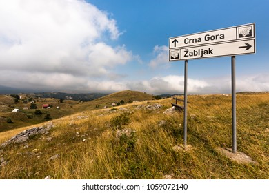 "Lovely hilly landscape on a touristic road through Durmitor National Park in the Dinaric Alps with signposts to the villages ""Crna Gora"" and ""Zabljak"", Montenegro"