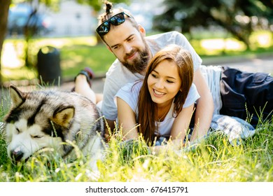 Lovely hipster couple with their alaskan malamute dog lying in the grass in hot summer day. Family, pet, animal and people concept.