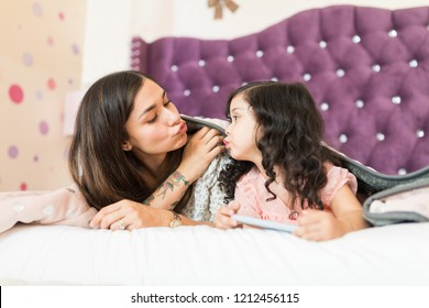 Lovely and Hispanic mother and daughter puckering while looking at each other in bed at home