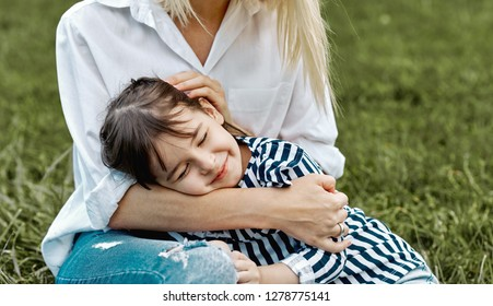 Lovely image of cute little child girl lying on her mother's legs outside. Loving mother and daughter sitting on the green grass in the park. Mom and kid cuddling. Good relationship. Mother's day