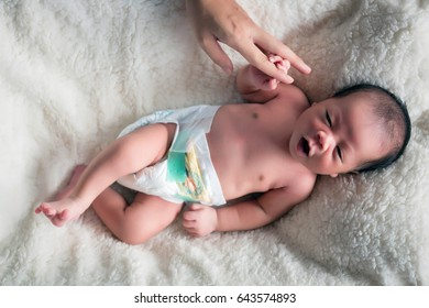 lovely Infant in bassinet is drowsy in gentlely touch and holding fingers hand of mom in mind emotional.