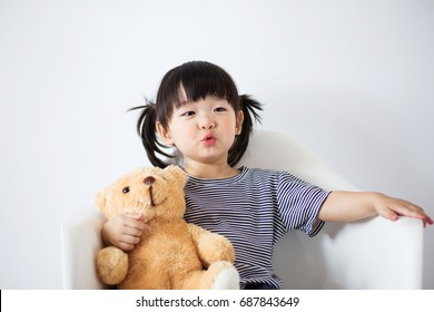Lovely and innocent asian kid playing with teddy happily