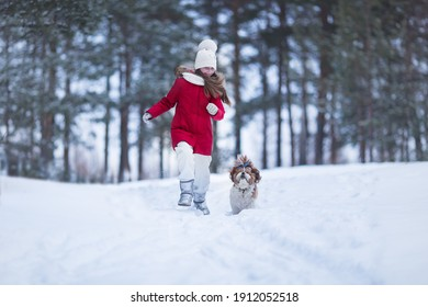 Lovely joyful girl running with a dog in the winter forest