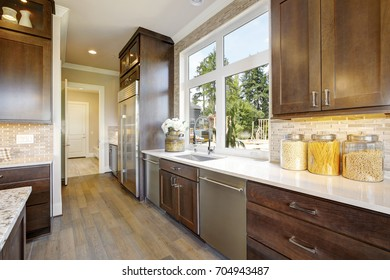 Lovely kitchen features wood cabinets fitted with high-end appliances paired with a white quartz countertop fitted with a sink and a gooseneck faucet and mosaic backsplash. Northwest, USA