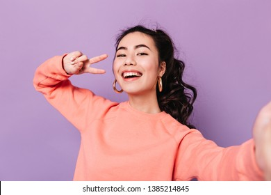 Lovely korean girl posing with peace sign. Laughing asian young woman taking selfie on purple background.