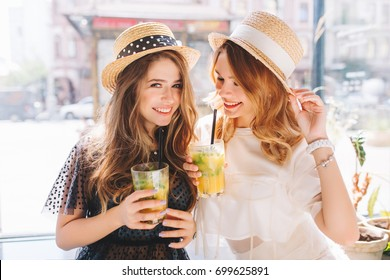 Lovely ladies wears similar straw hats having fun together enjoying icy fruit cocktails in summer day. Indoor portrait of two female friends smiling and joking in cafe while drink juice.