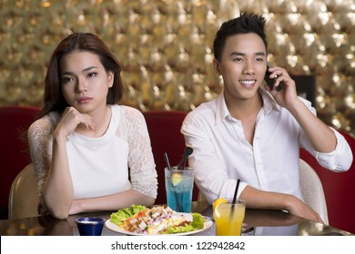 Lovely lady being annoyed with her boyfriend talking on the phone in the middle of the date