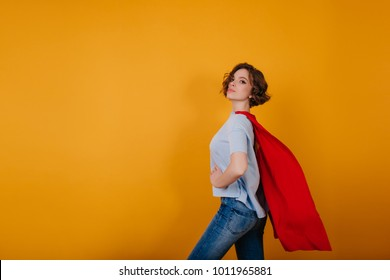 Lovely lady with curly hairstyle ready for new year carnival. Portrait of attractive superwoman in red mantle isolated on yellow background.