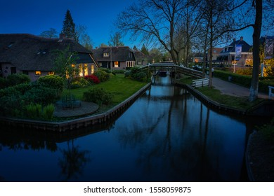 Lovely landscape at night with canal and illuminated windows, Giethoorn, Netherlands