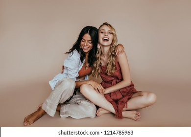 Lovely latin girl sitting on the floor with sister. Elegant blonde female model joking with best friend.