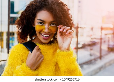 Lovely laughing black woman posing outdoor on modern district background. Wearing stylish yellow glasses and sweater.