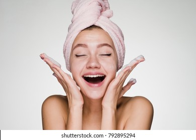 lovely laughing girl with a pink towel on her head applies cleansing foam on her face
