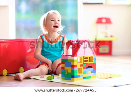 Lovely laughing little child, blonde girl of preschool age playing with colorful blocks sitting on a floor in a sunny room with a big window at home or kindergarten