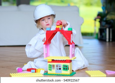Lovely laughing little child, preschool age toddler girl wearing safety helmet playing indoors building house with colorful blocks sitting on a floor in big playroom at home or kindergarten