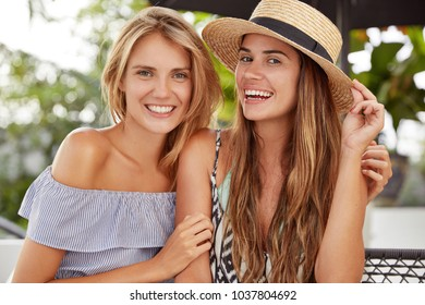 Lovely lesbians laugh and cuddle while spend nice time together, sits against outdoor cafe interior, enjoy summer rest, have joyful expressions. Homosexuality and samesex relationships concept.