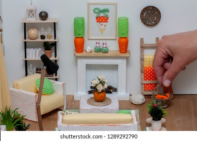 Lovely light dollhouse interior, Living room with white rustic furniture and bright decor, A hand putting a basket with carrots on the floor
