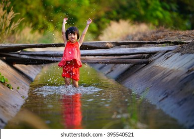 lovely little asian girl in red dress,playing water in the irrigation canal,