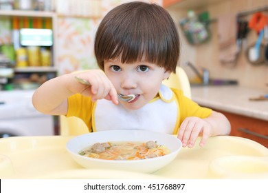 Lovely little boy eating soup with meat balls at home kitchen