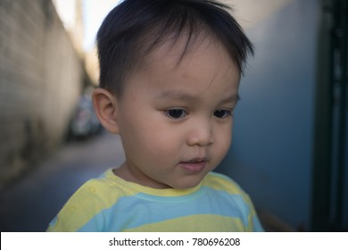lovely little boy playing in small alley way