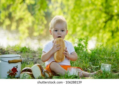 the lovely little boy sitting on a plaid and eating bread with milk