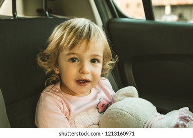 Lovely little girl in the back seat of a car. Children traveling in a car