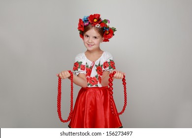 Lovely little girl with a charming smile in the Ukrainian national costume holding red beads on Beauty and Fashion