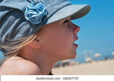 Lovely little girl in denim cap on the beach