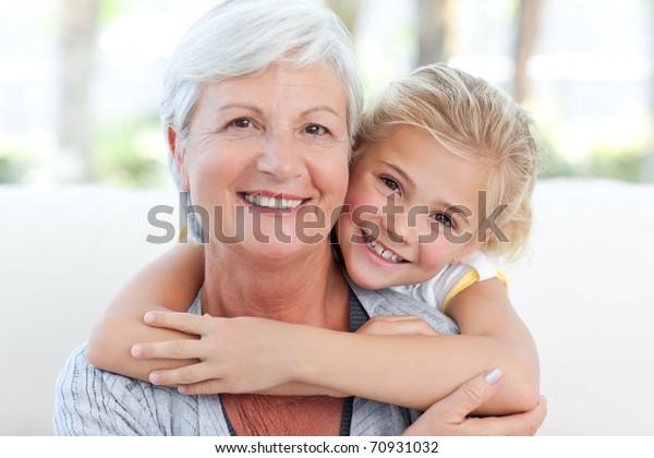 Encantadora niñita con su abuela mirando la cámara