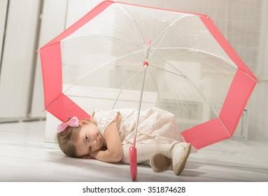 Lovely little girl lying down on the floor under an umbrella, indoor shot on white room