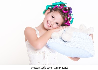 Lovely little girl in pajamas sleeping on pillow in hair curlers, glamour child,bedtime. Funny little girl portrait. isolated on white background, studio.