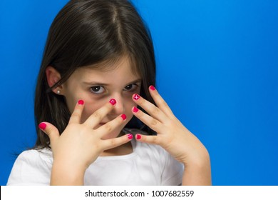 Lovely little girl proudly shows her pink polish nails looking at camera over blue background. Princess kid game, child manicure concept