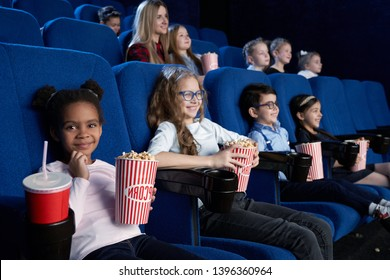 Lovely little girl sitting in cinema, looking at camera and smiling while watching movie. Small african girl eating popcorn and drinking aerated sweet water. Cocept of entertainment.