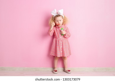 Lovely little girl in a striped red and white dress and bunny ears on her  head 781d95c1f
