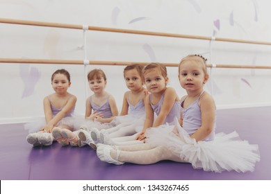 Lovely little girls looking to the camera, sitting on the floor at ballet school. Adorable little ballerinas rest after exercising. Group of little dancers wearing leotards relaxing after ballet