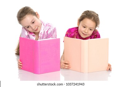 Lovely little girls are reading a book. The concept of education and education, family and people. Isolated on white background.