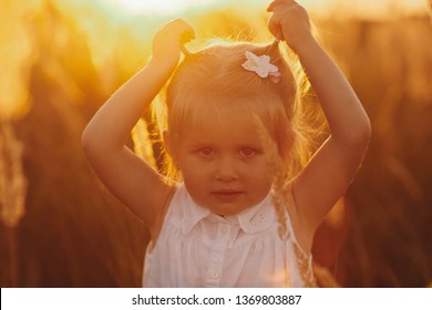 A lovely little smiling girl in a wreath of chamomiles in the flowering field in a sunny summer day. little pretty girl in the field